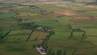 AX113_025 - 6K stock footage aerial video of farm fields and rural homes, Kilmarnock, Scotland at sunrise