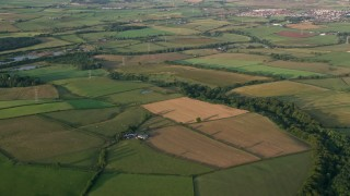 AX113_027 - 6K stock footage aerial video approach and fly over farms and fields in Kilmarnock, Scotland at sunrise