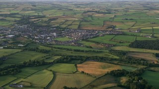 AX113_028 - 6K stock footage aerial video of farm fields around a village, Tarbolton, Scotland at sunrise