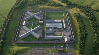 AX113_033 - 6K stock footage aerial video of orbiting Kilmarnock Prison in Scotland at sunrise