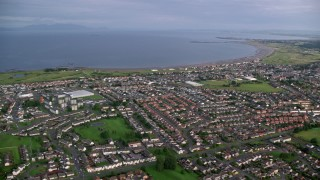 AX113_036 - 6K stock footage aerial video of homes and apartment buildings near Firth of Clyde, Prestwick, Scotland
