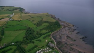 AX113_043 - 6K stock footage aerial video of farm fields and a RV park near coastal cliffs along Firth of Clyde, Ayr, Scotland