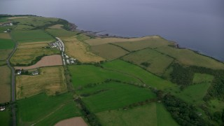 AX113_044 - 6K stock footage aerial video of coastal farm fields and RV Park along Firth of Clyde, Ayr, Scotland