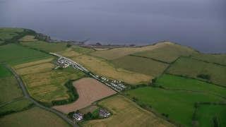 AX113_045 - 6K stock footage aerial video of farm fields and RV Park by Firth of Clyde, Ayr, Scotland