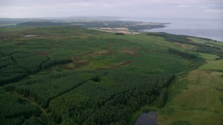 AX113_048 - 6K stock footage aerial video pan across forest and moor near the Firth of Clyde, Ayr, Scotland