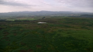 AX113_050 - 6K stock footage aerial video of green moorland and Drumshang Loch in Ayr, Scotland