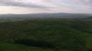 AX113_051 - 6K stock footage aerial video of green, hilly moorland in Ayr, Scotland