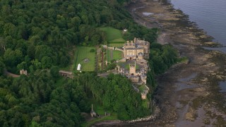 AX113_055 - 6K stock footage aerial video of Culzean Castle by trees and Firth of Clyde, Maybole, Scotland