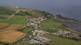 AX113_058 - 6K stock footage aerial video flyby coastal village and RV park along Firth of Clyde, Maidens, Scotland