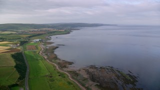 AX113_063 - 6K stock footage aerial video of coastline and farmland along Firth of Clyde, Girvan, Scotland