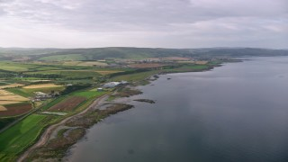 AX113_064 - 6K stock footage aerial video of coastline and farming fields along Firth of Clyde, Girvan, Scotland