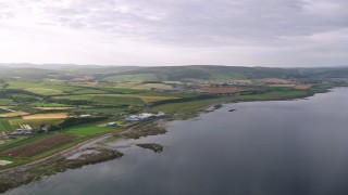 AX113_065 - 6K stock footage aerial video of the coastline and farms along Firth of Clyde, Girvan, Scotland