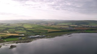 AX113_066 - 6K stock footage aerial video of passing the coastline and farms along Firth of Clyde, Girvan, Scotland