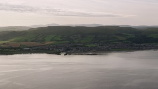 AX113_072 - 6K stock footage aerial video of the coastal town of Girvan seen from Firth of Clyde, Scotland