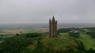 AX113_137 - 6K stock footage aerial video of orbiting Scrabo Tower atop a green hill, Newtownards, Northern Ireland
