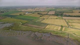 AX113_139 - 6K stock footage aerial video flying by farm fields, reveal shoreline, Newtownards, Northern Ireland