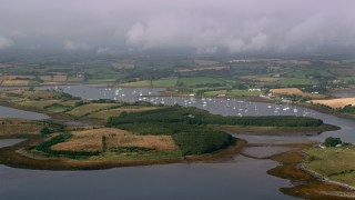AX113_147 - 6K stock footage aerial video of islands and boats in a harbor in the Strangford Lough, Northern Ireland