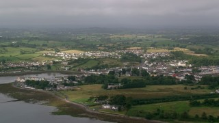 AX113_151 - 6K stock footage aerial video flyby a village and farmland along Strangford Lough, Killyleagh, Northern Ireland