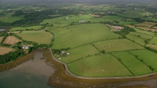AX113_154 - 6K stock footage aerial video of farm fields on the shore of Strangford Lough, Killyleagh, Northern Ireland
