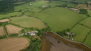 AX113_155 - 6K stock footage aerial video orbiting farms and farm fields, Killyleagh, Northern Ireland