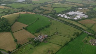 AX113_163 - 6K stock footage aerial video fly over farms and fields near a country road, Downpatrick, Northern Ireland