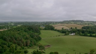 AX113_168 - 6K stock footage aerial video of trees and farmland, Downpatrick, Northern Ireland