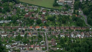 AX114_002 - 6K stock footage aerial video of homes in a village neighborhood, Banstead, England