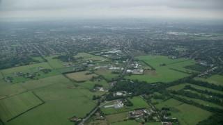 AX114_003 - 6K stock footage aerial video tilt from farmland and reveal residential neighborhoods, Wallington, England