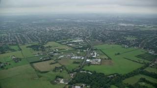 AX114_004 - 6K stock footage aerial video fly over farm fields toward residential neighborhoods, Wallington, England