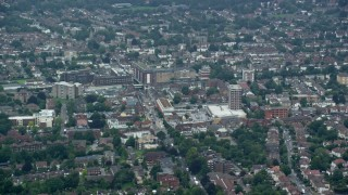 AX114_005 - 6K stock footage aerial video of flying by apartment buildings and a shopping center, Wallington, England