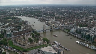 AX114_049 - 6K stock footage aerial video approach Tower of London and the Tower Bridge over River Thames, England