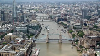 AX114_093 - 6K stock footage aerial video orbit the Tower Bridge on River Thames, reveal skyscrapers in Central London, England