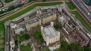 AX114_102 - 6K stock footage aerial video tilt to bird's eye of tourists at the Tower of London, England