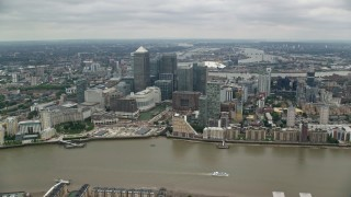 AX114_129 - 6K stock footage aerial video of crossing the River Thames toward Canary Wharf skyscrapers, London, England