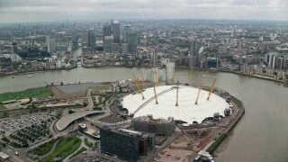 AX114_140 - 6K stock footage aerial video orbit The O2 arena, with Canary Wharf skyscrapers in background, London, England