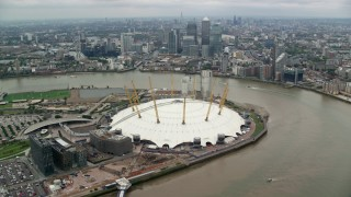 AX114_141 - 6K stock footage aerial video of O2 Arena with Canary Wharf skyscrapers in background, London, England