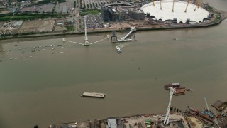 AX114_143 - 6K stock footage aerial video of orbit Emirates Air Line gondolas and reveal The O2 arena, London, England