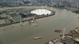 AX114_144 - 6K stock footage aerial video orbit Emirates Air Line gondolas near The O2 Arena, London, England