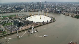 AX114_145 - 6K stock footage aerial video fly over gondolas to approach The O2 arena and Canary Wharf skyscrapers, London, England