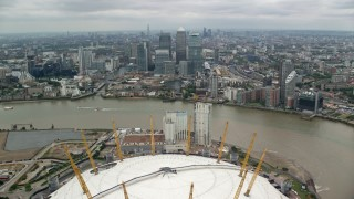 AX114_147 - 6K stock footage aerial video fly over O2 arena, approach Canary Wharf skyscrapers, London, England
