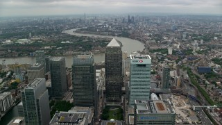 AX114_151 - 6K stock footage aerial video fly over Canary Wharf skyscrapers toward River Thames, London, England