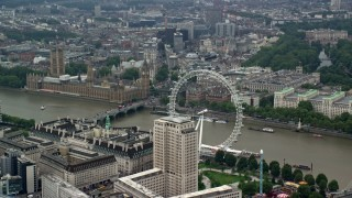 AX114_183 - 6K stock footage aerial video of iconic Big Ben, British Parliament and London Eye by River Thames, England