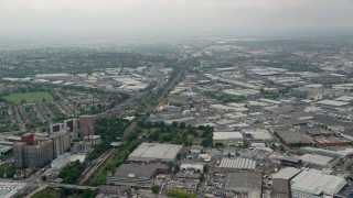 AX114_272 - 6K stock footage aerial video of flying over warehouses near train tracks and A40 Highway, London, England