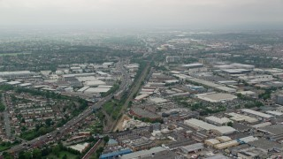 AX114_273 - 6K stock footage aerial video fly over warehouses and train tracks near the A40 highway, London, England