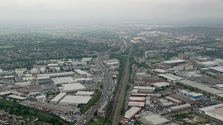 AX114_274 - 6K stock footage aerial video of flying over warehouses, train tracks and A40 highway, London, England