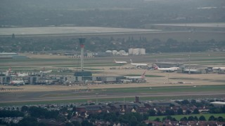 AX114_286 - 6K stock footage aerial video of control tower and aircraft at London Heathrow Airport, England