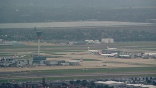 AX114_287 - 6K stock footage aerial video of the control tower and airliner at London Heathrow Airport, England