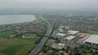 AX114_296 - 6K stock footage aerial video of passing M4 Freeway by warehouses and reservoir, Slough, England