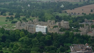 AX114_319 - 6K stock footage aerial video of a reverse view of Windsor Castle among trees, England