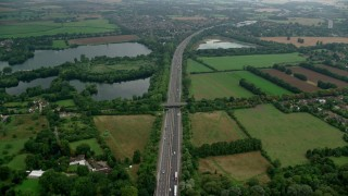 AX114_328 - 6K stock footage aerial video of an orbit of M4 freeway and farmland near Bray Lake, Maidenhead, England Day
